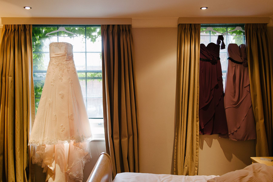wedding dress hung up with bridemaid dresses inside hotel du vin poole