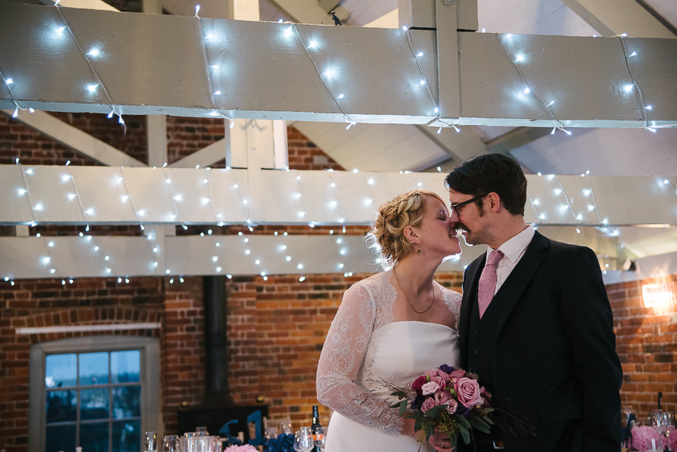 Jo and Andy dinosaur themed winter wedding at sopley mill kissing